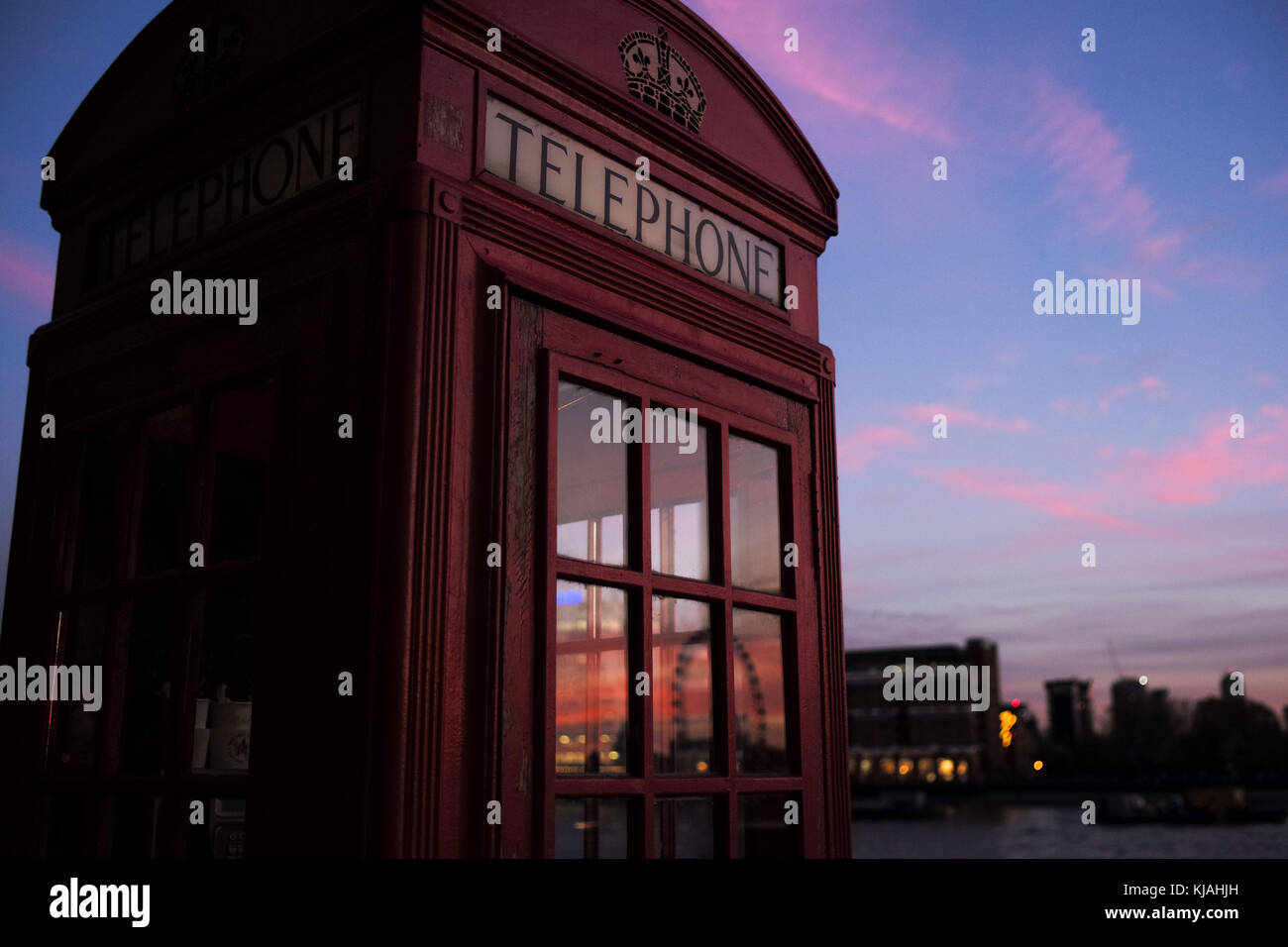 Traditional English telephone red box in London with sunset reflected in windows. - Stock Image