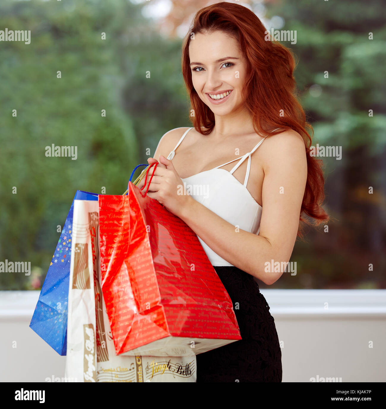 Beautiful girl holding shopping bags - Stock Image