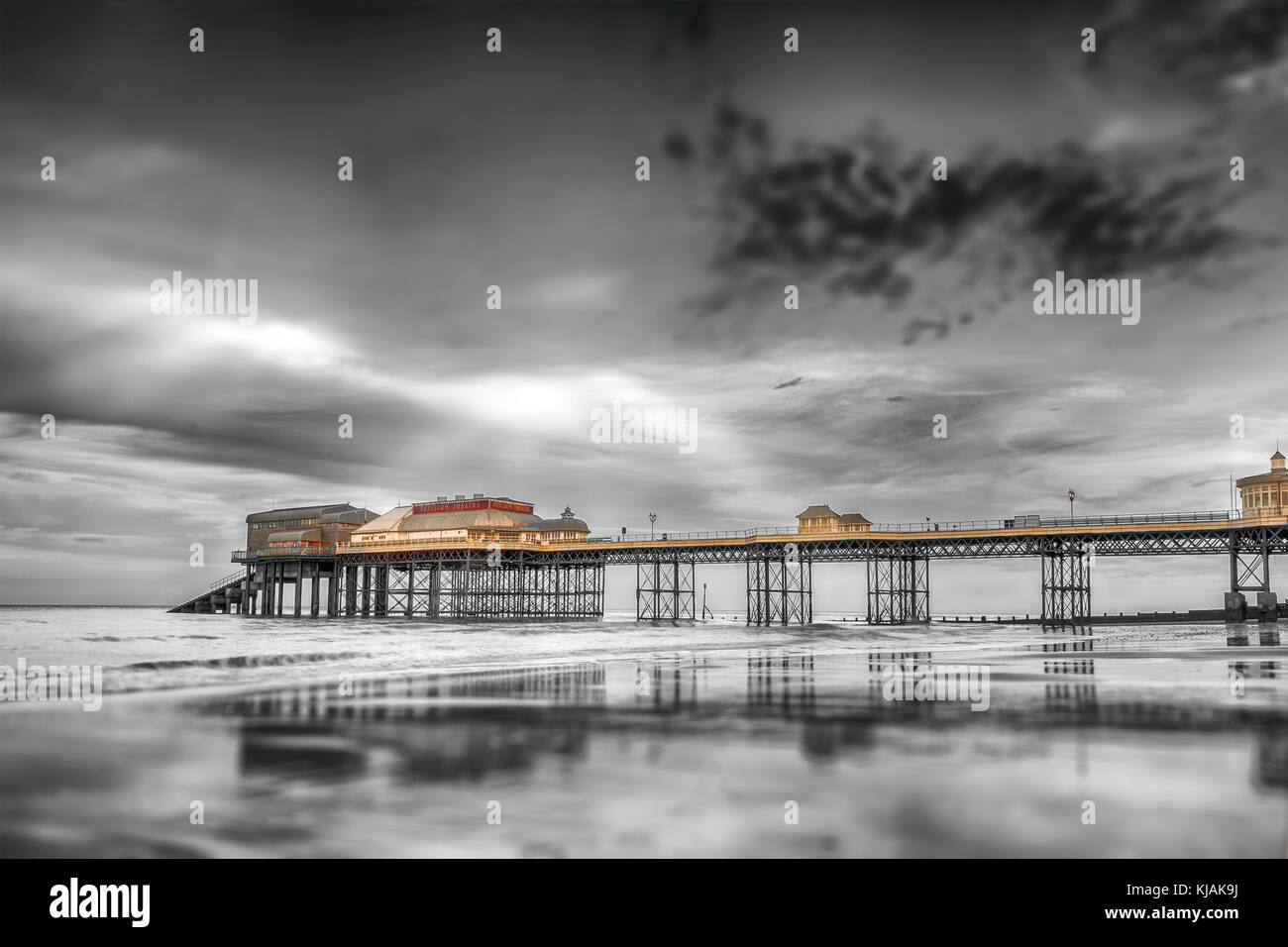 Historic Norfolk Cromer pier reflecting into the sea in black and white. Sunlight escaping the clouds and illuminating - Stock Image