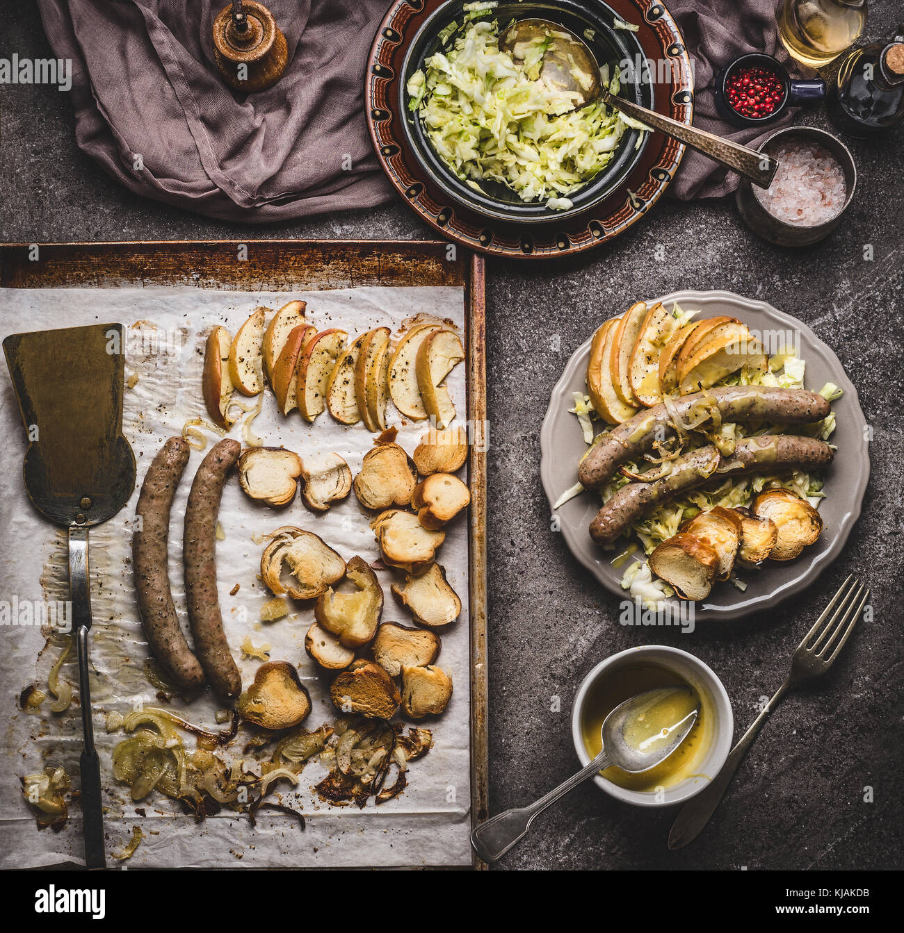 Fried sausages on baking tray served on plate with white coleslaw salad and mustard dip on rustic kitchen table, top view. German food concept. Stock Photo