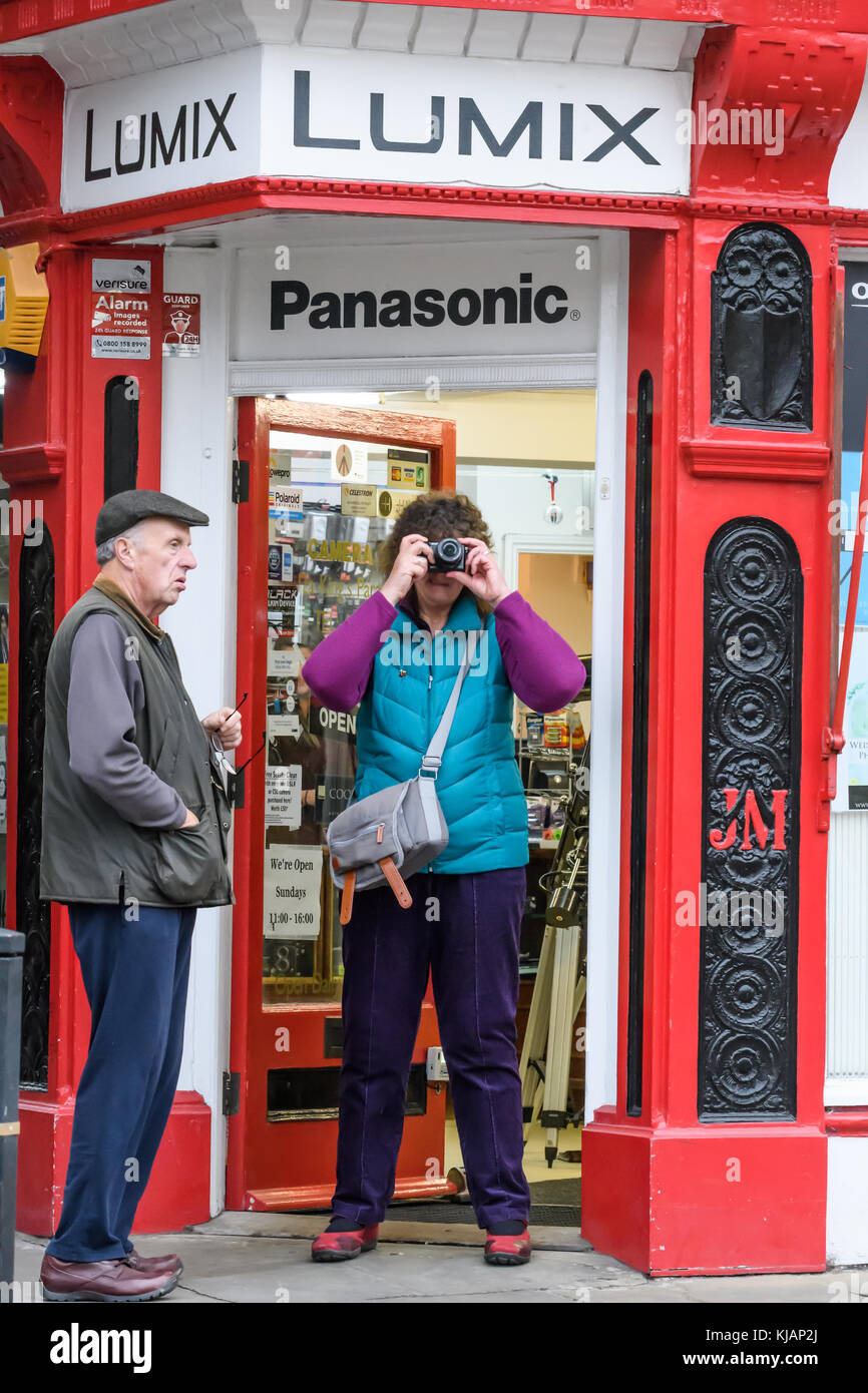A couple of potential purchasers examine a camera in the doorway of Campkin's camera shop on King's parade - Stock Image