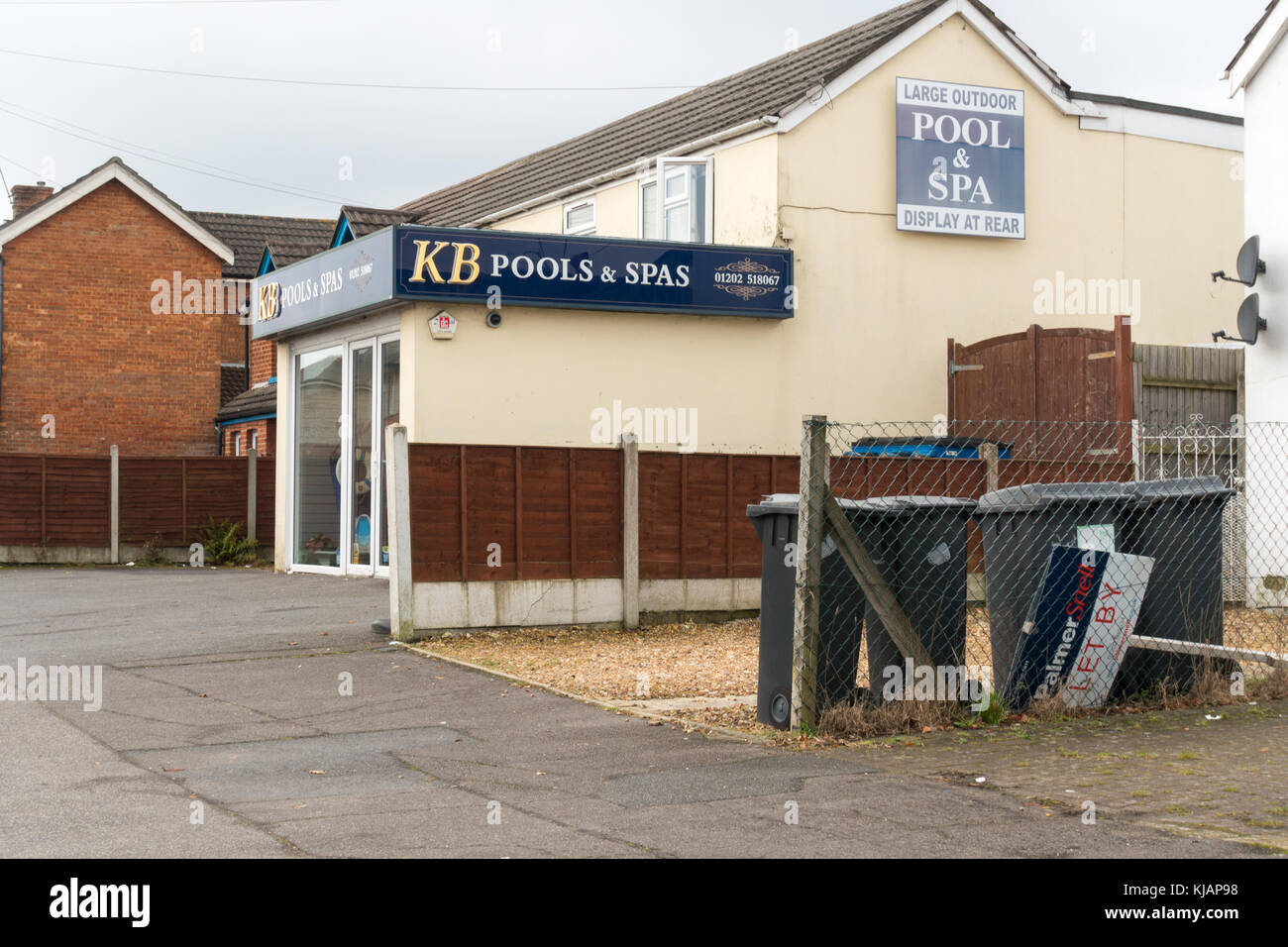 Refuse (wheelie) bins next door to a pools & spas showroom in Wallisdown, United Kingdom - Stock Image