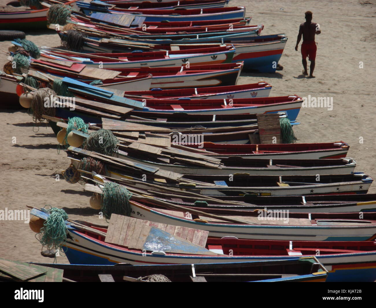 A man walking on tarrafal beach in cape verde, among colored small wooden boats aligned on the sand Stock Photo