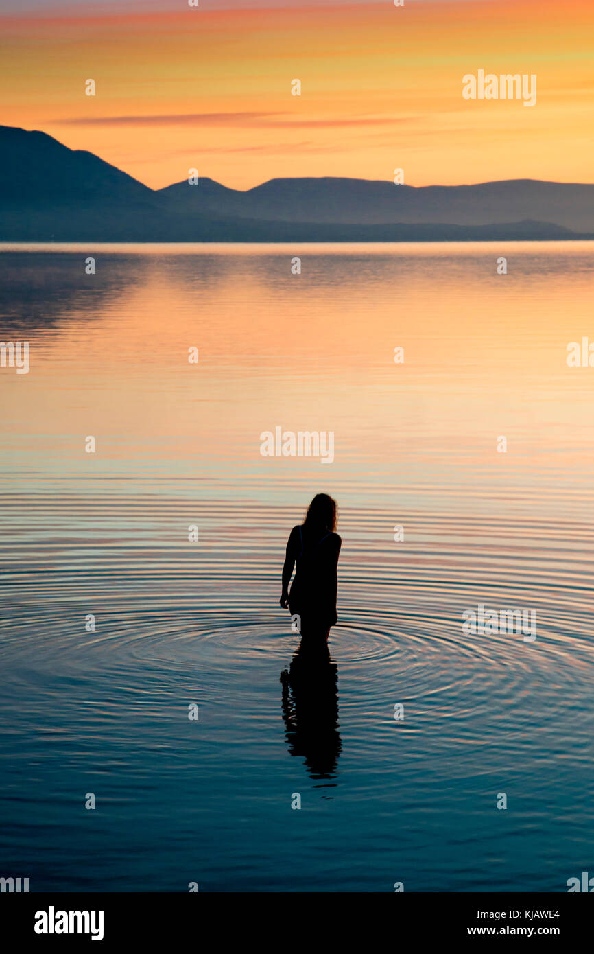 A lone woman bather is reflected as she enters the calm water of the Aegean sea. She is silhouetted against the - Stock Image