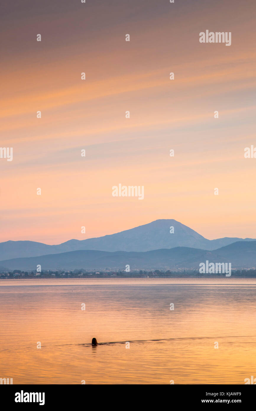 The orange colored dawn sky is reflected in the calm sea as a lone bather swims in front of Mount Olympus in Greece. - Stock Image