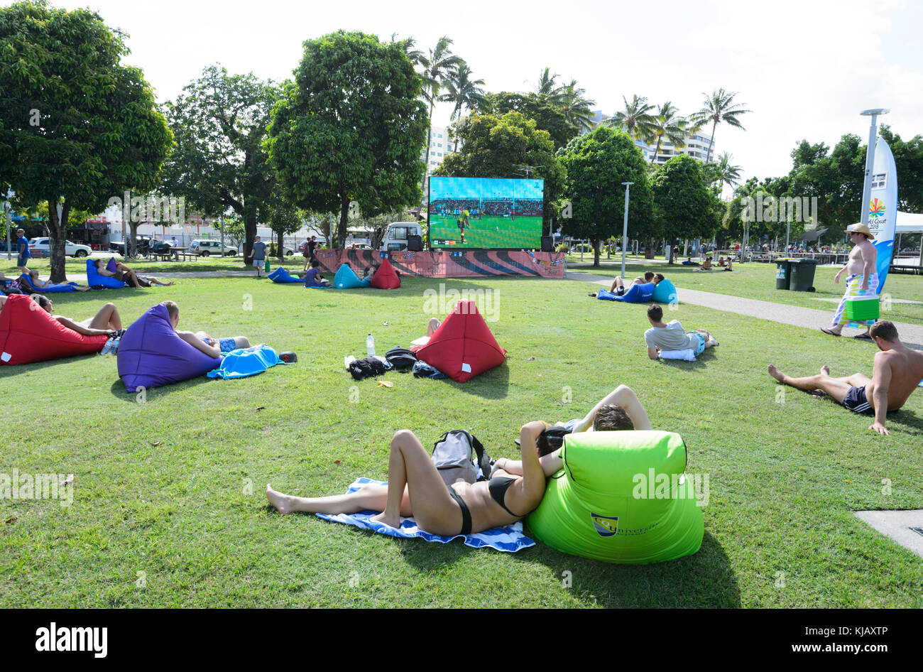 People leisurely watching a rugby match on a giant TV screen from their inflatable air couch on Cairns Esplanade, - Stock Image
