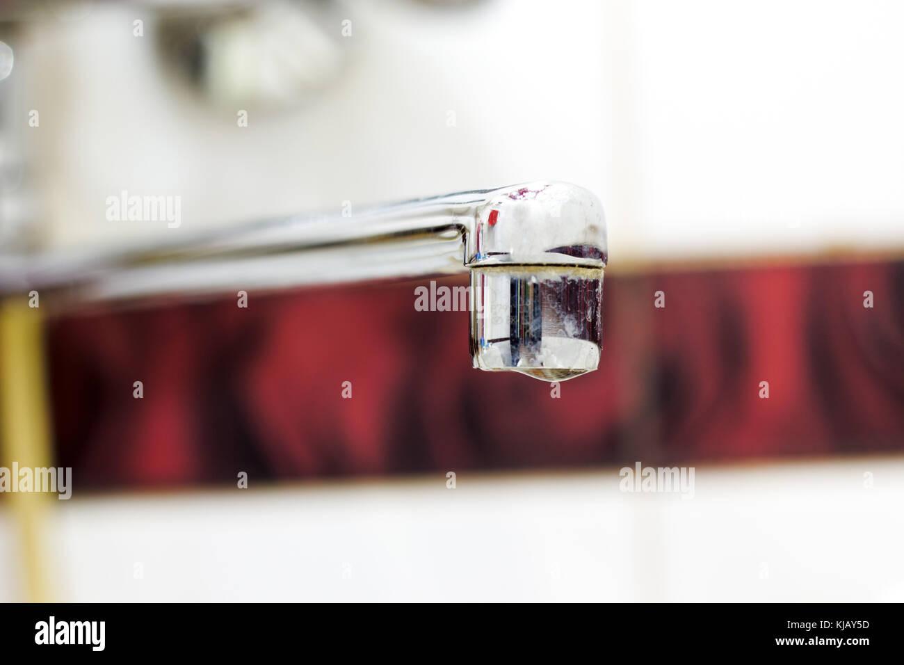 Metal tap and water drop close up - Stock Image