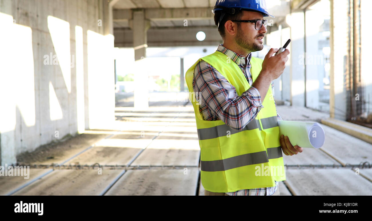Male architect with blueprints using walkie-talkie - Stock Image