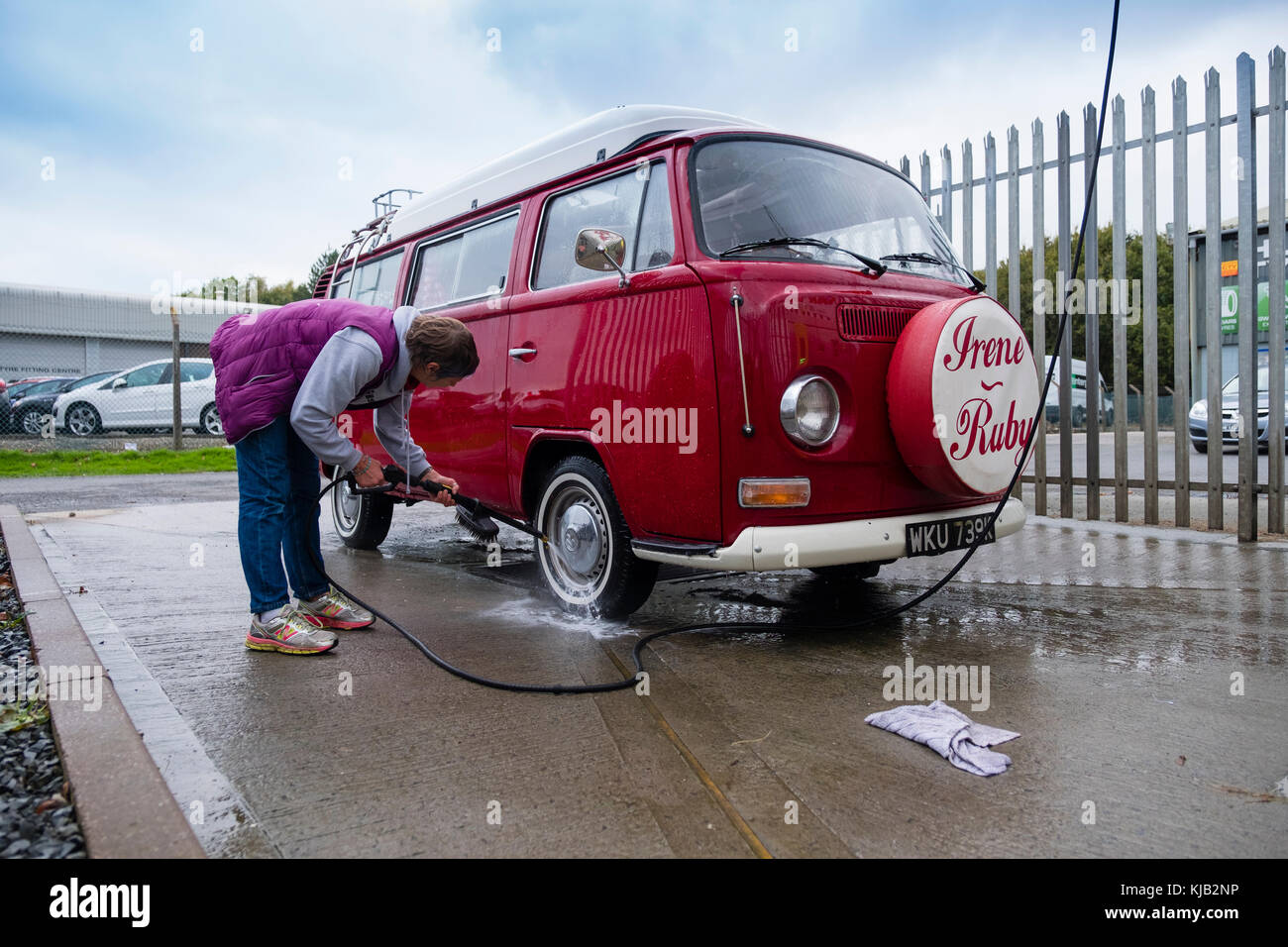 A middle aged woman at a self service coin operated car wash a middle aged woman at a self service coin operated car wash washing her classic red volkswagen vw type 2 t2 bay window campervan uk solutioingenieria Images
