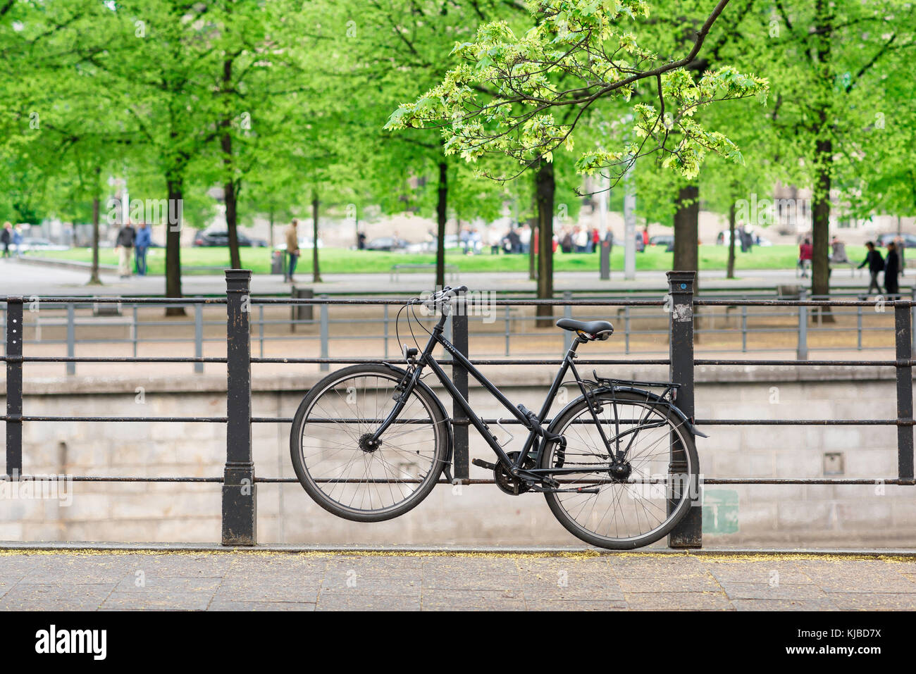 A black bicycle chained to railings near the Lustgarten park in Berlin, Germany, Europe - Stock Image