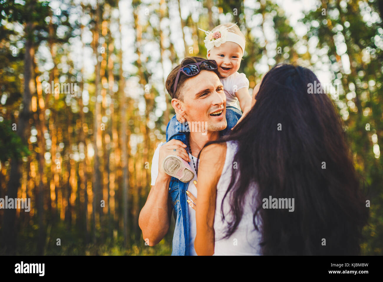 stylish young Family of mom, dad and daughter one year old blonde sitting near father on shoulders, outdoors outside - Stock Image