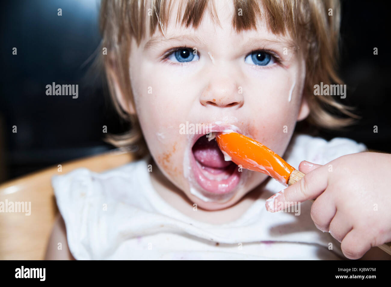 Messy child eating with a spoon - Stock Image