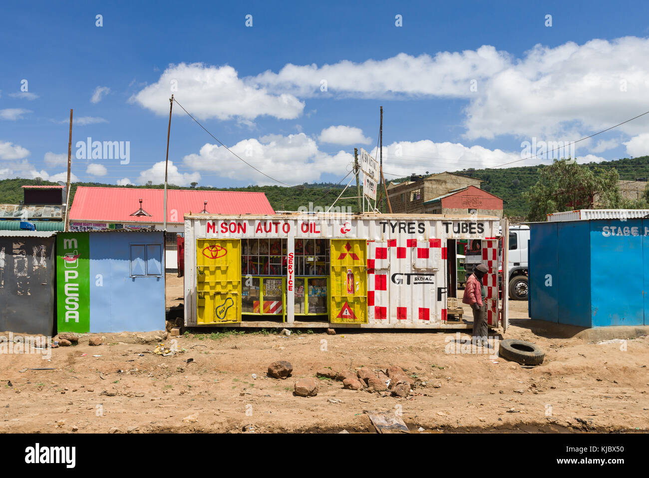 An African man stands by a shop made from a reused shipping container by the roadside, Kenya, East Africa - Stock Image