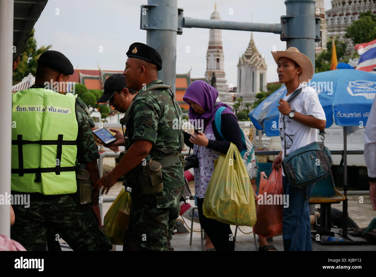 Thai people embark on a public boat from a pier along the Chao Praya, Bangkok, accompanied by soldiers. - Stock Image