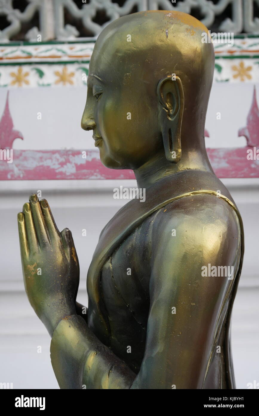 A side-profile picture of a statue of a golden Buddha praying in Wat Arun, the Temple of Dawn, in Bangkok, Thailand. - Stock Image