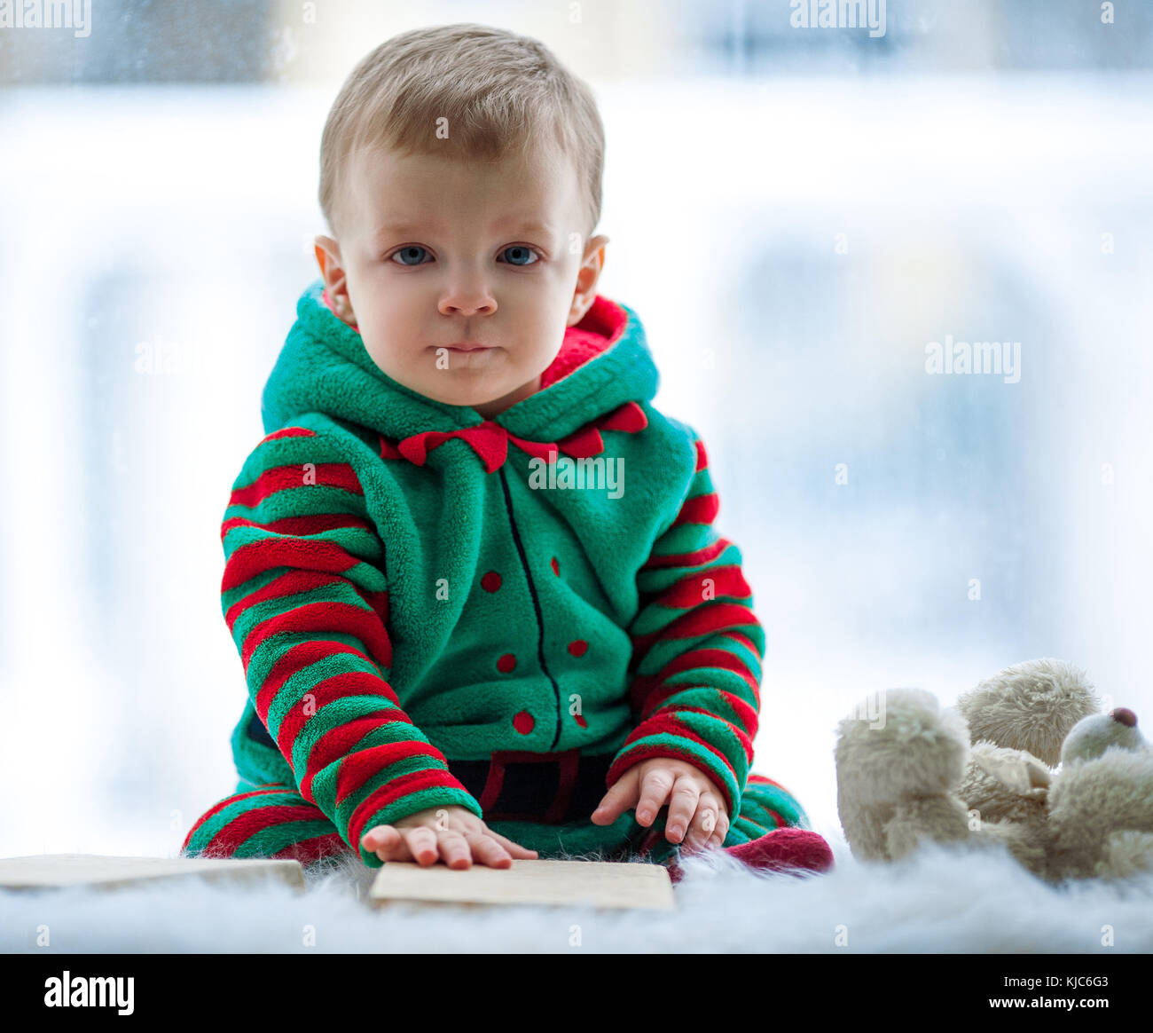 Little boy in red and green rompers with teddy bear sits on background of window. - Stock Image