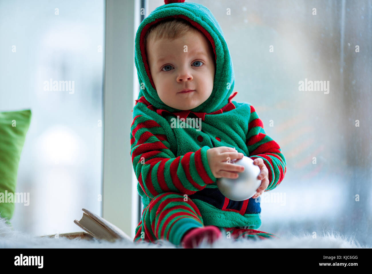 Little boy in red and green rompers with ball sits on background of window. - Stock Image