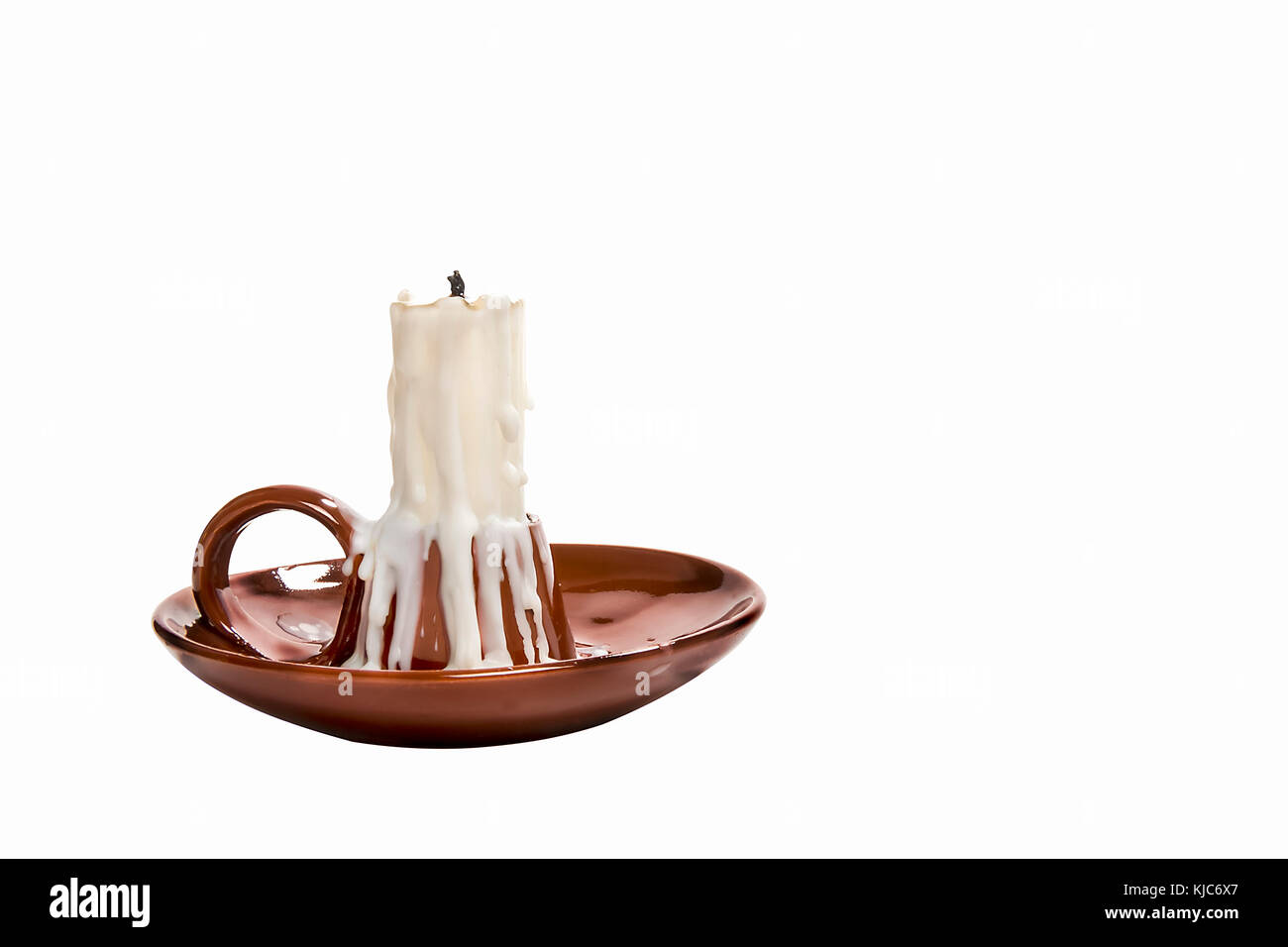 unlit candle in candlestick on white background - Stock Image