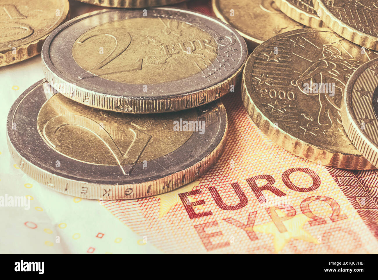 Some coins of euro on a banknote of ten euros. - Stock Image