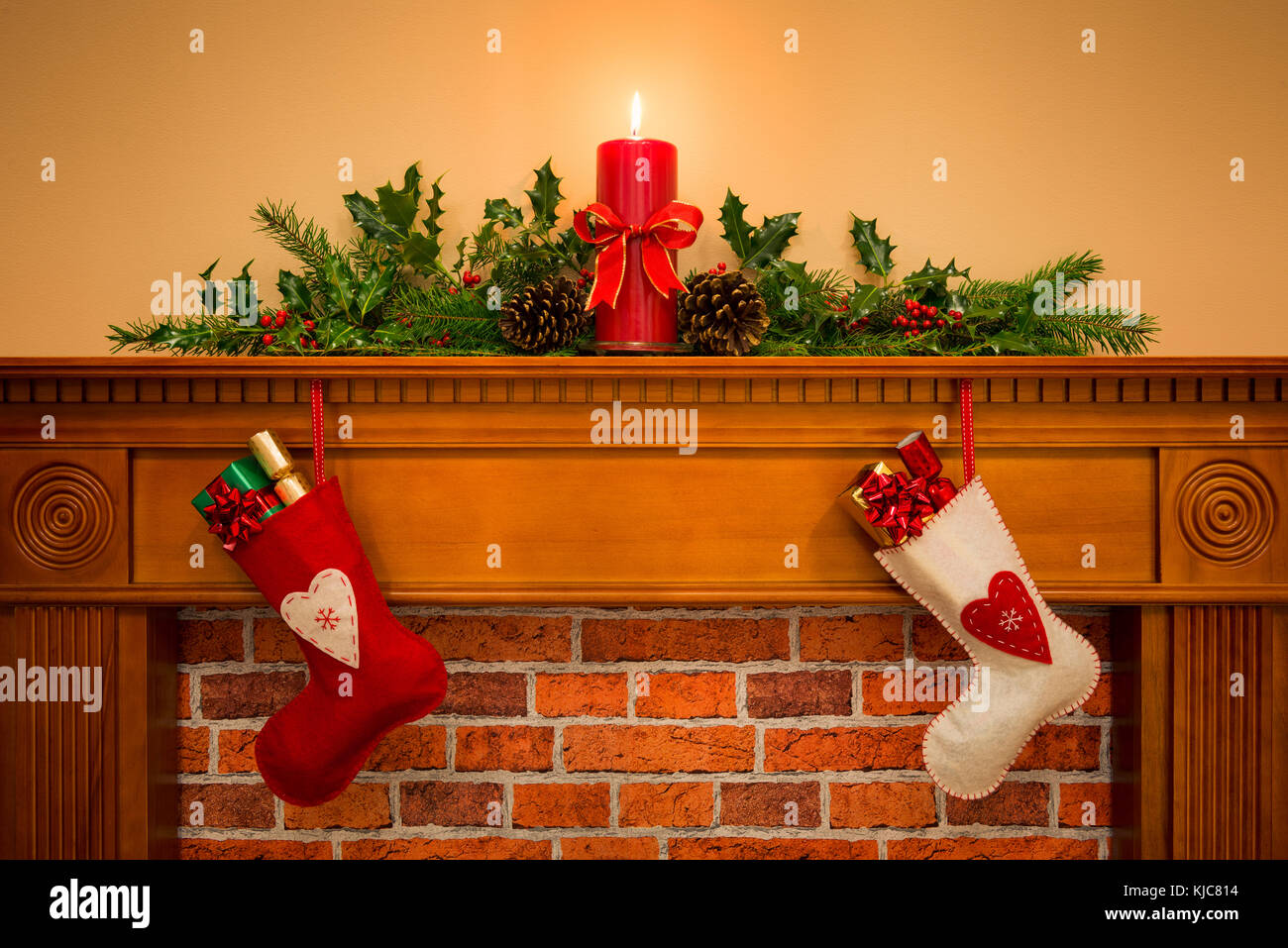 Two Christmas stockings with gift wrapped presents hanging on a mantelpiece over a fireplace, plus burning candle Stock Photo