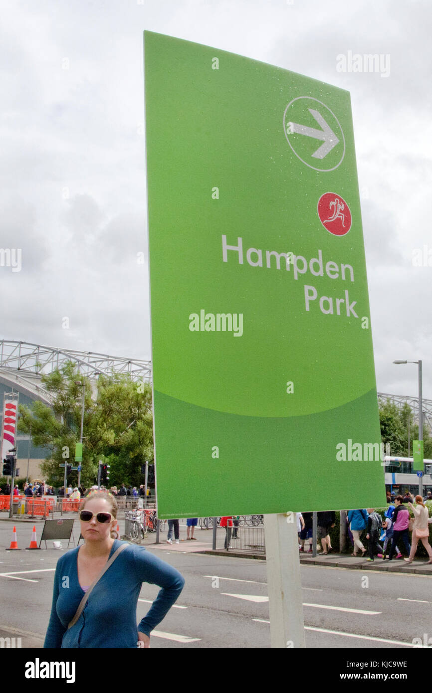 GLASGOW, SCOTLAND - JULY 29 2014: A girl stands next to a .Hampden Park sign during the Glasgow Commonwealth Games Stock Photo