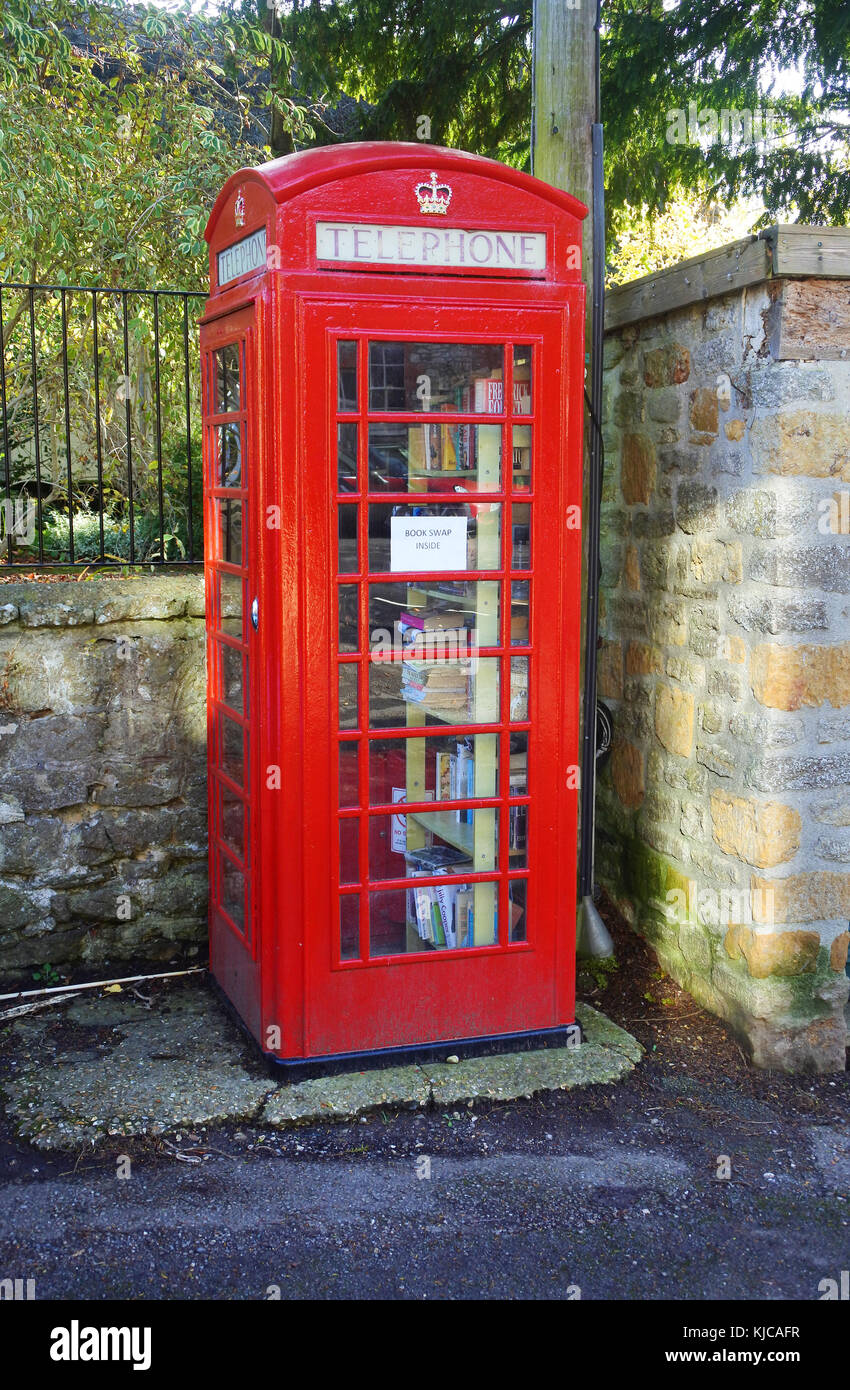 Tradition, old fashioned red telephone box now used as a book swapping location, Netherbury, Dorset, UK - John Gollop Stock Photo