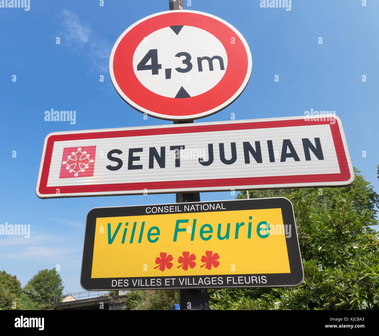 Town sign for Saint Junien (Sent Junian in Occitan) with Ville Fleurie 3 flower notice, Haute-Vienne, France, Europe - Stock Image