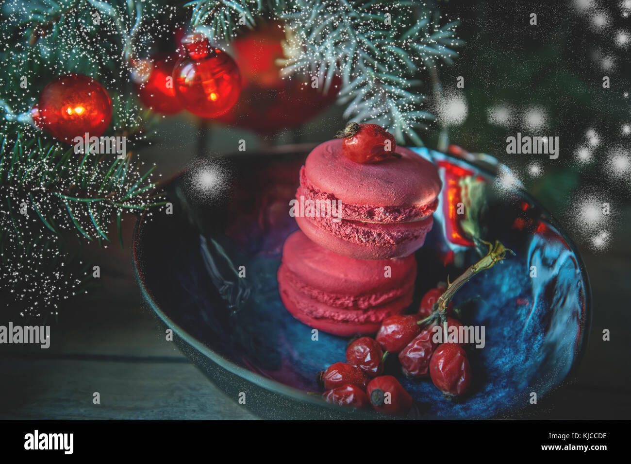 Fresh red macaron with berries of wild rose on the Christmas tree branches tables. Snow. Copy spaces. The horizontal - Stock Image