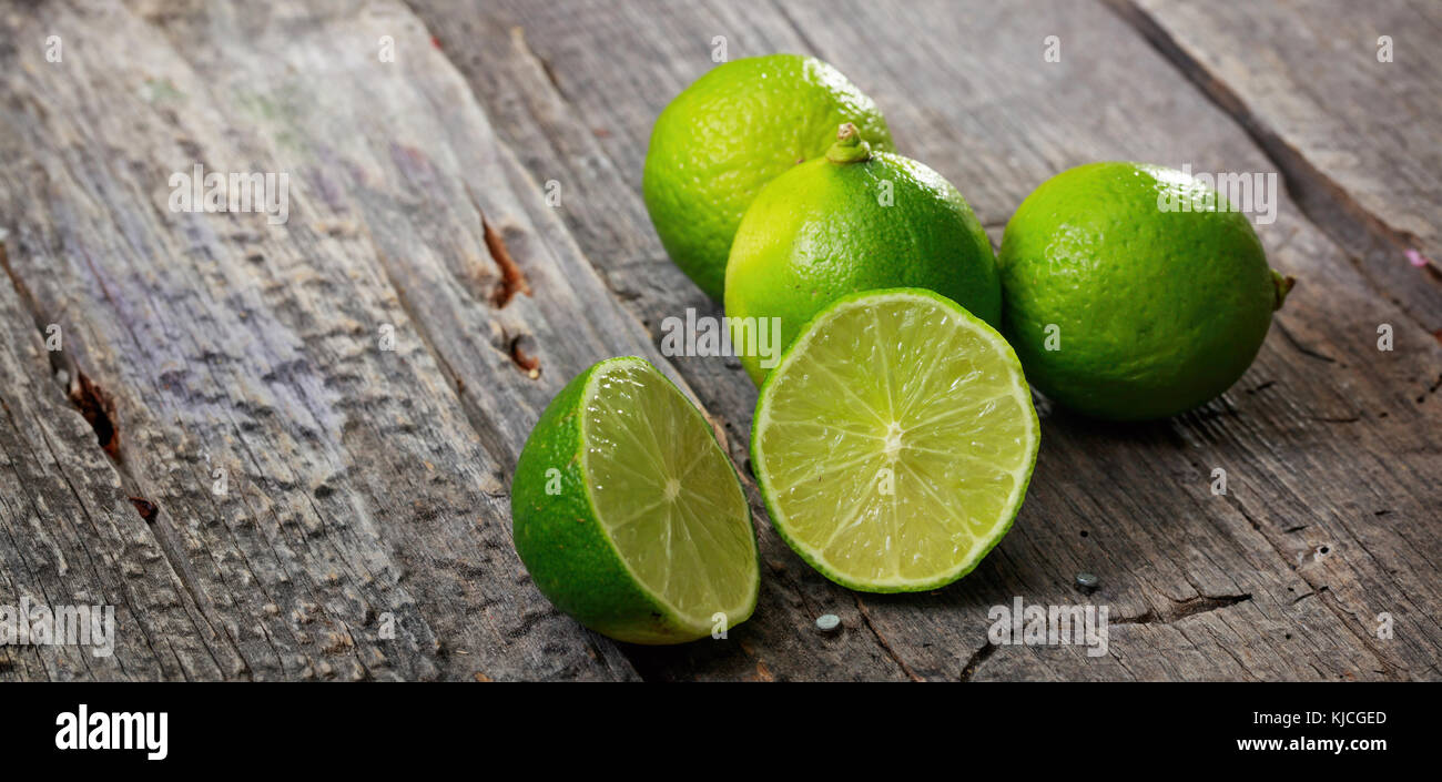 Cut and whole limes on wooden table, copy space - Stock Image
