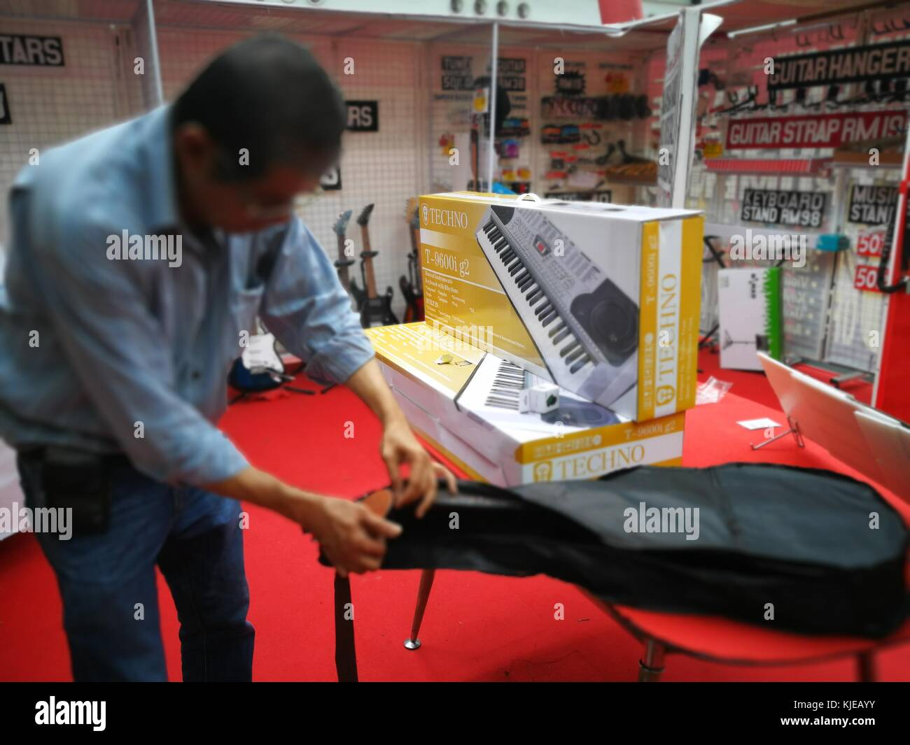 Selangor, Malaysia - 21 November 2017: Shop owner is packing the newly bought guitar into the case at Musical Instruments - Stock Image