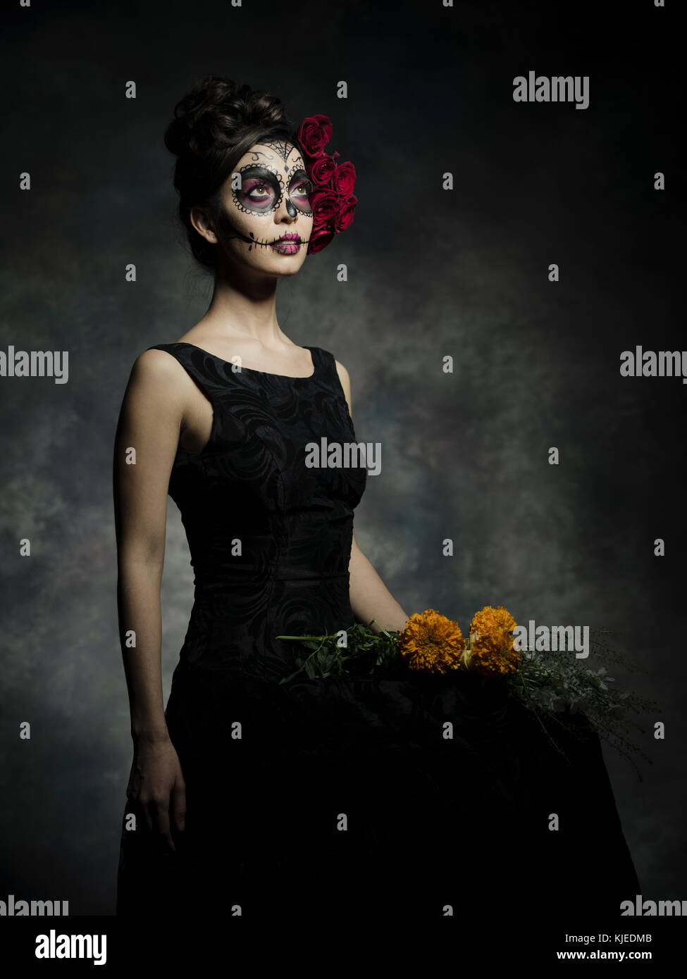 Beautiful Mexican American woman celebrating Día de los Muertos ( Día de Muertos ) is the Mexican holiday also known as Day of the Dead with skull makeup and roses in the style of Catrina. Stock Photo
