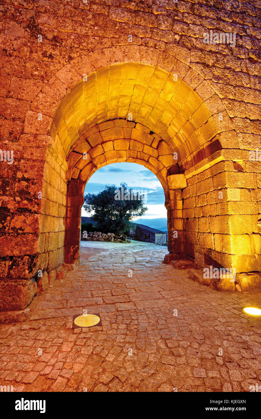 Nocturnal illuminated medieval town gate with cobblestone paved alley - Stock Image