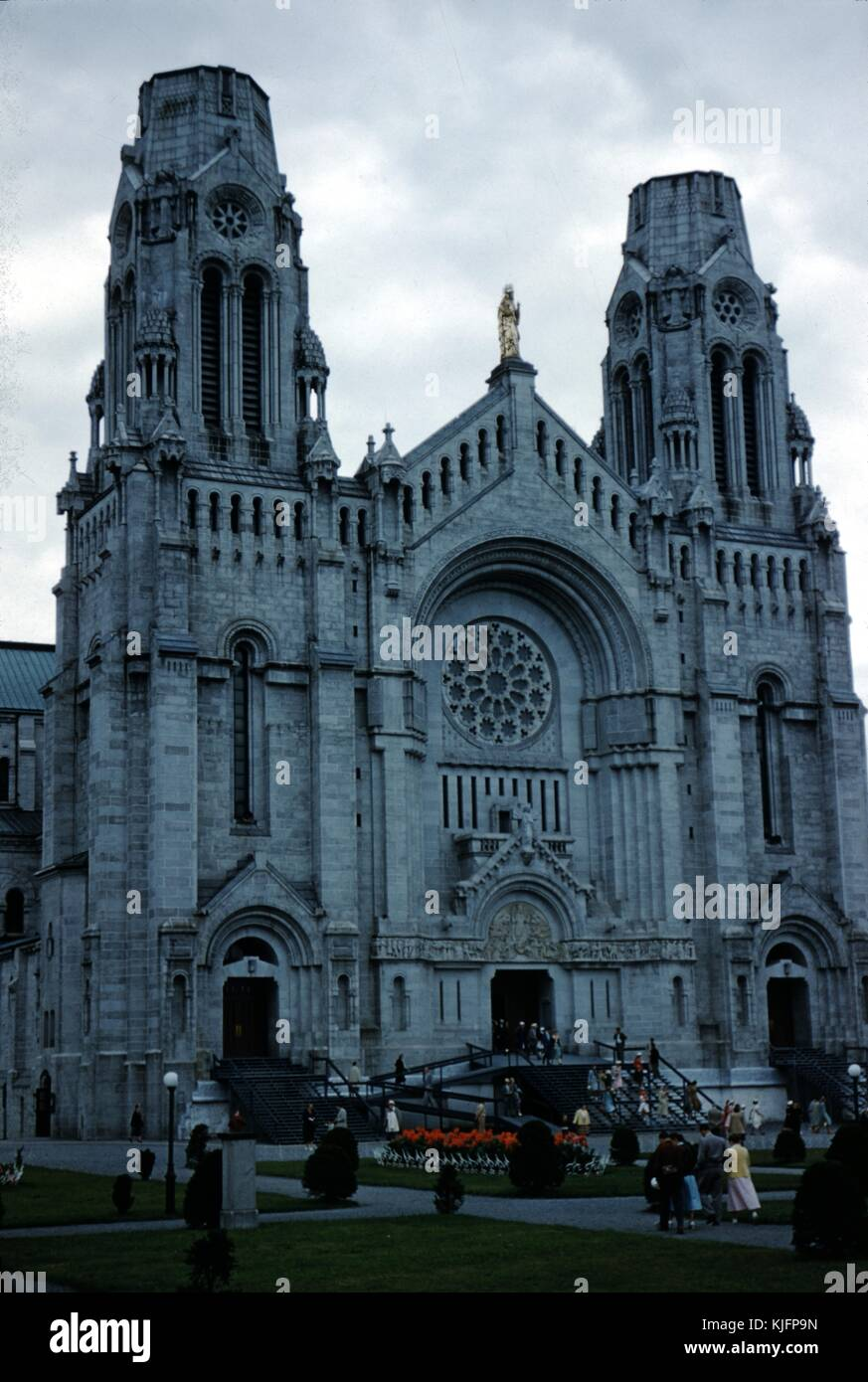 Color photograph of Sainte-Anne-de-Beaupre Cathedral, groups of people walking toward it, Quebec, Canada, 1952. - Stock Image