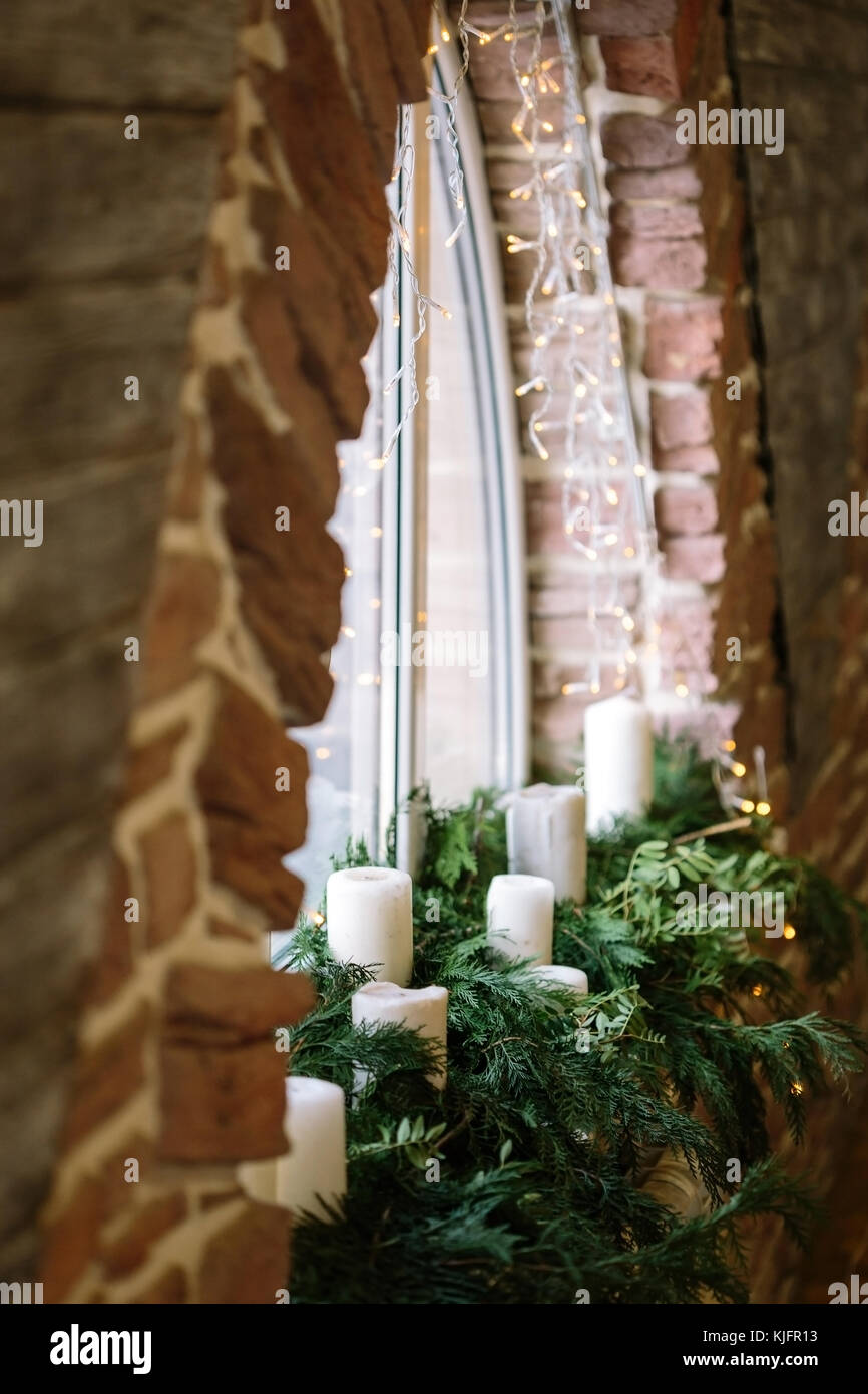 interior, winter, holidays concept. red bricks of the wall surround window in form of semicircle with fresh fuzzy - Stock Image