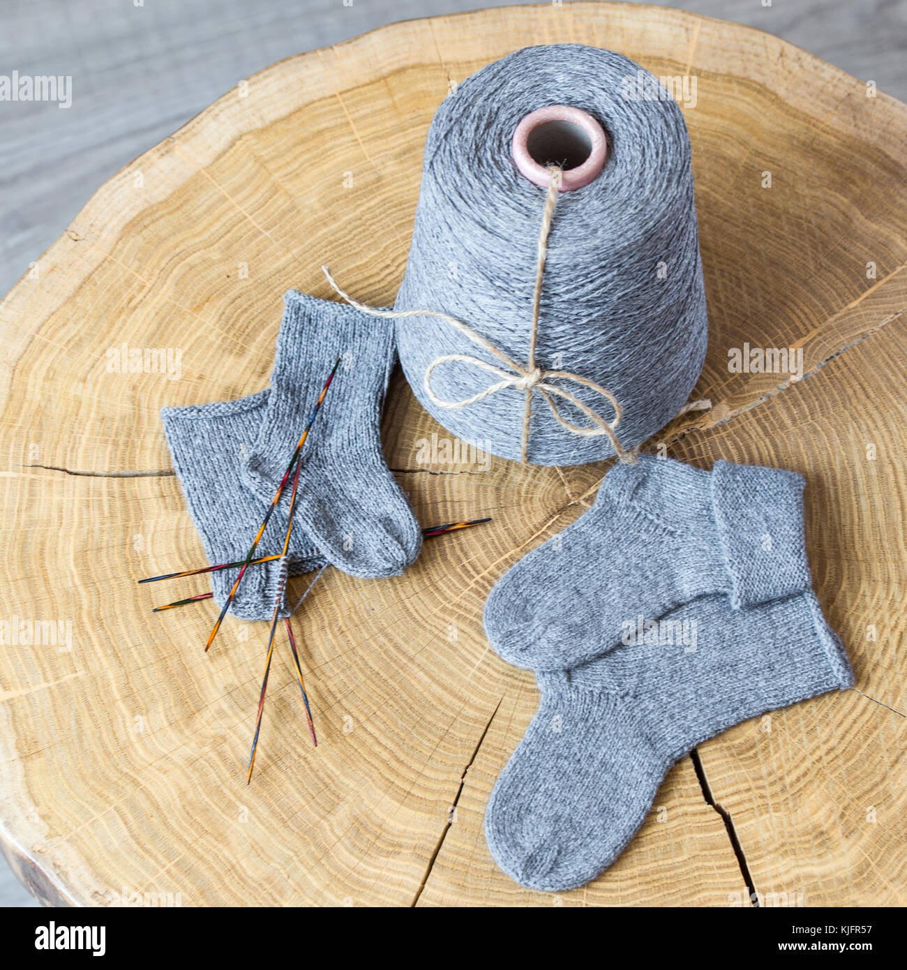 Cone of grey fluffy cashmere, knitting needles and newborn baby ...