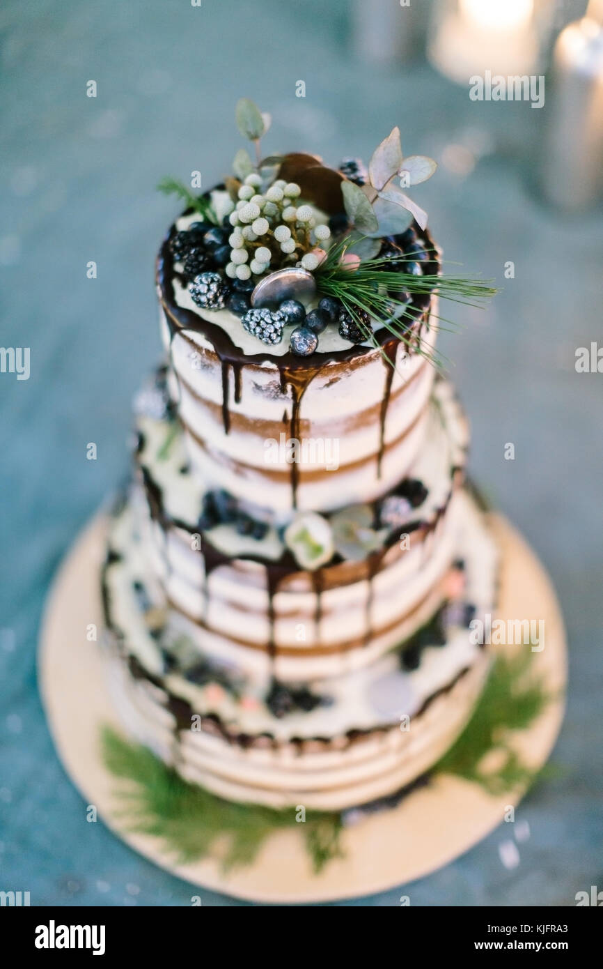confectionary, cooking, handmade concept. close up of treat for wedding, richly decorated cake with dark frosting, - Stock Image