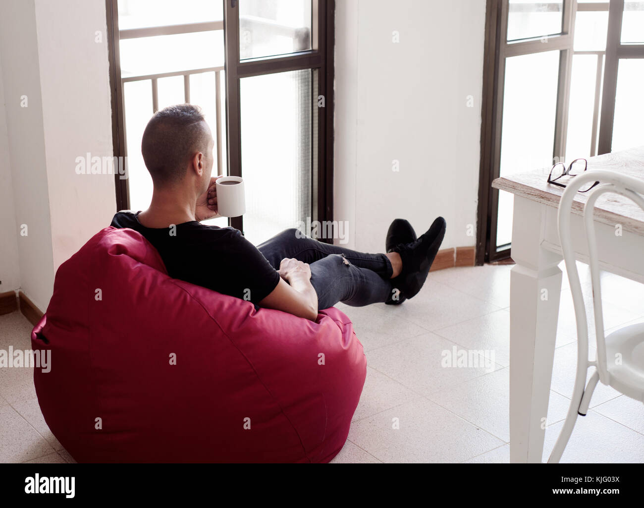 a young caucasian man indoors have a coffee sitting in a comfortable red bean bag chair - Stock Image