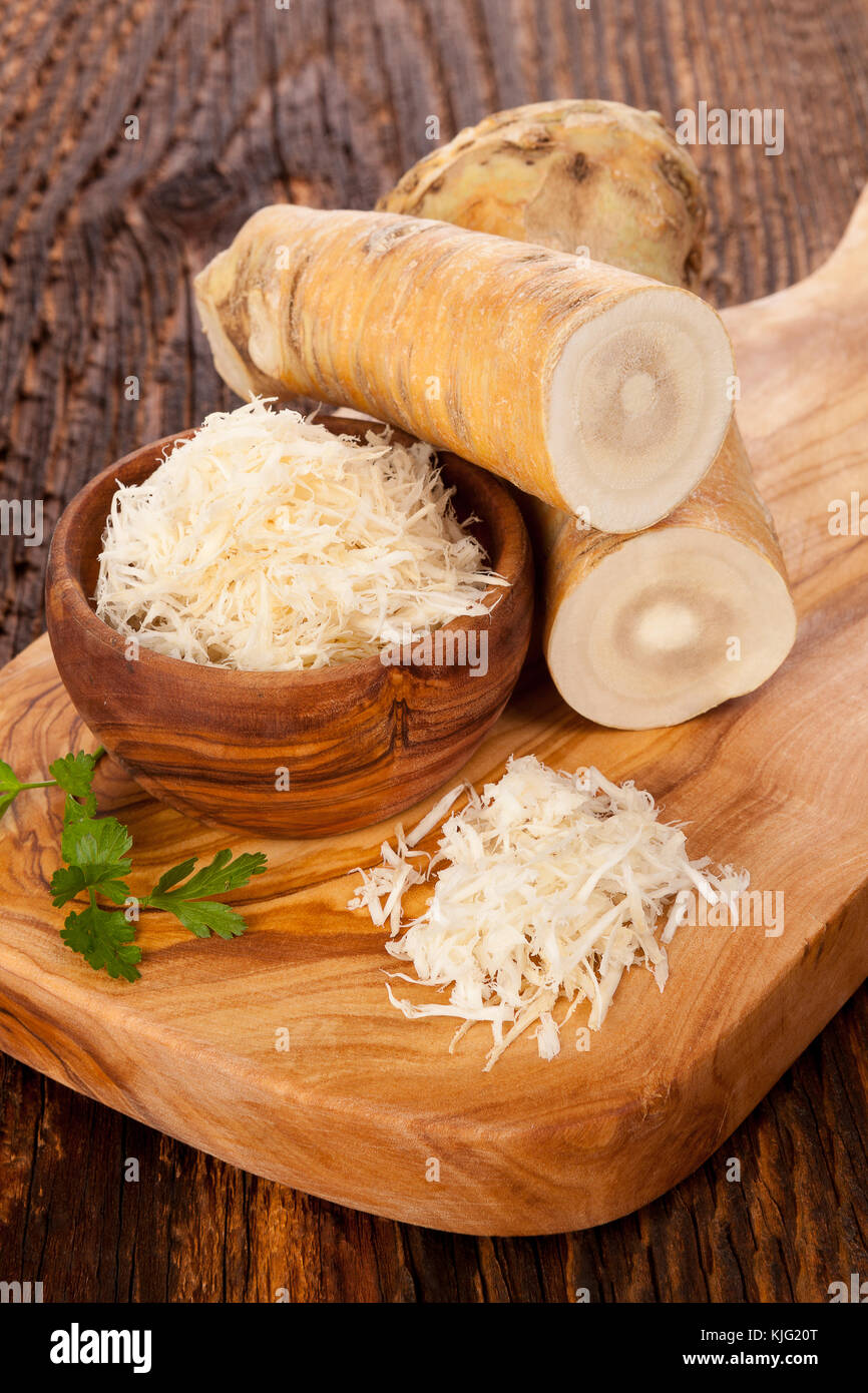 Fresh and grated horseradish in wooden bowl with parsley on wooden background.. - Stock Image