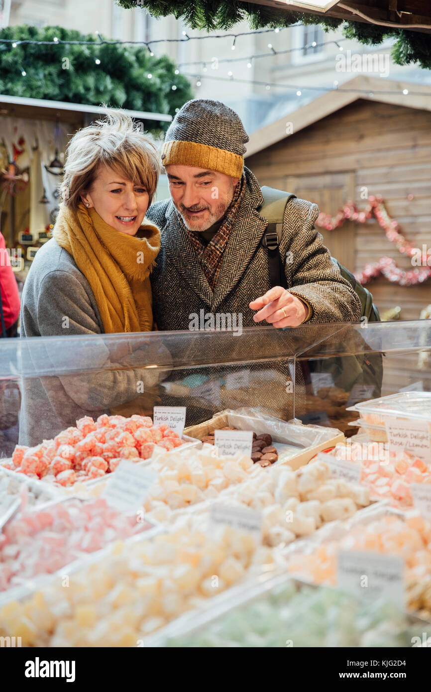 Mature couple are choosing which turkish delight to buy at a christmas market. Stock Photo
