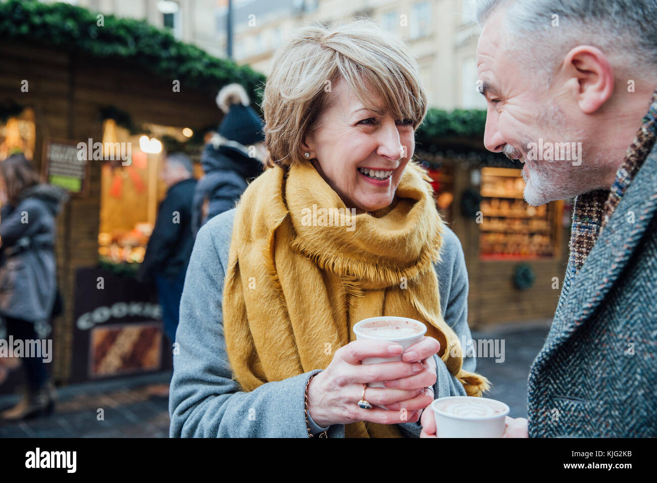 Mature couple are enjoying a cup of coffee as they explore the town christmas market. Stock Photo