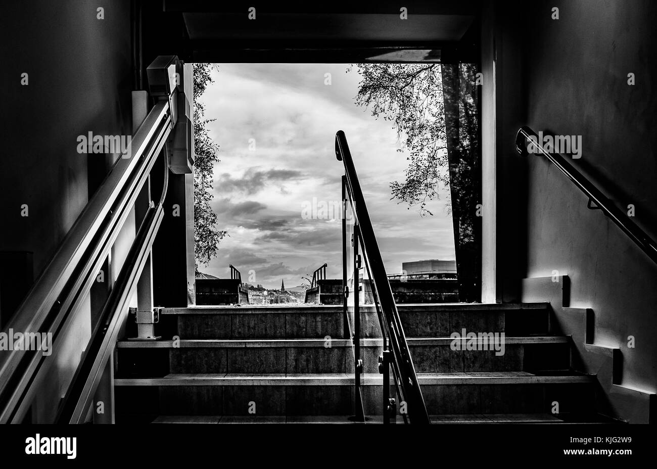 Stairway leading up to external view of town buildings in black and white - Stock Image