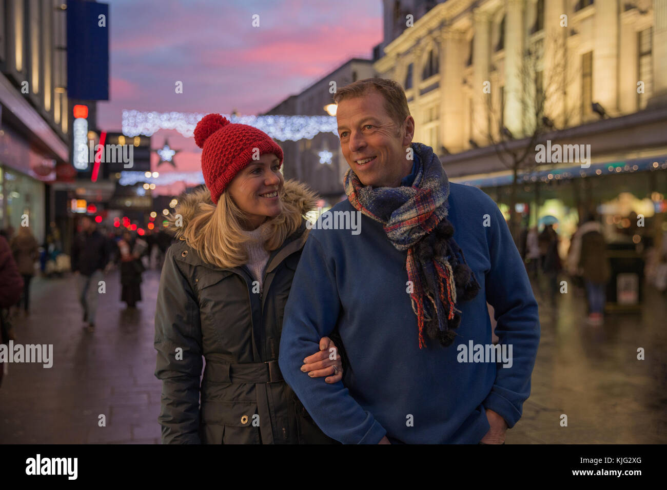 Mature couple are enjoying an evening stroll through town at Christmas time. Stock Photo