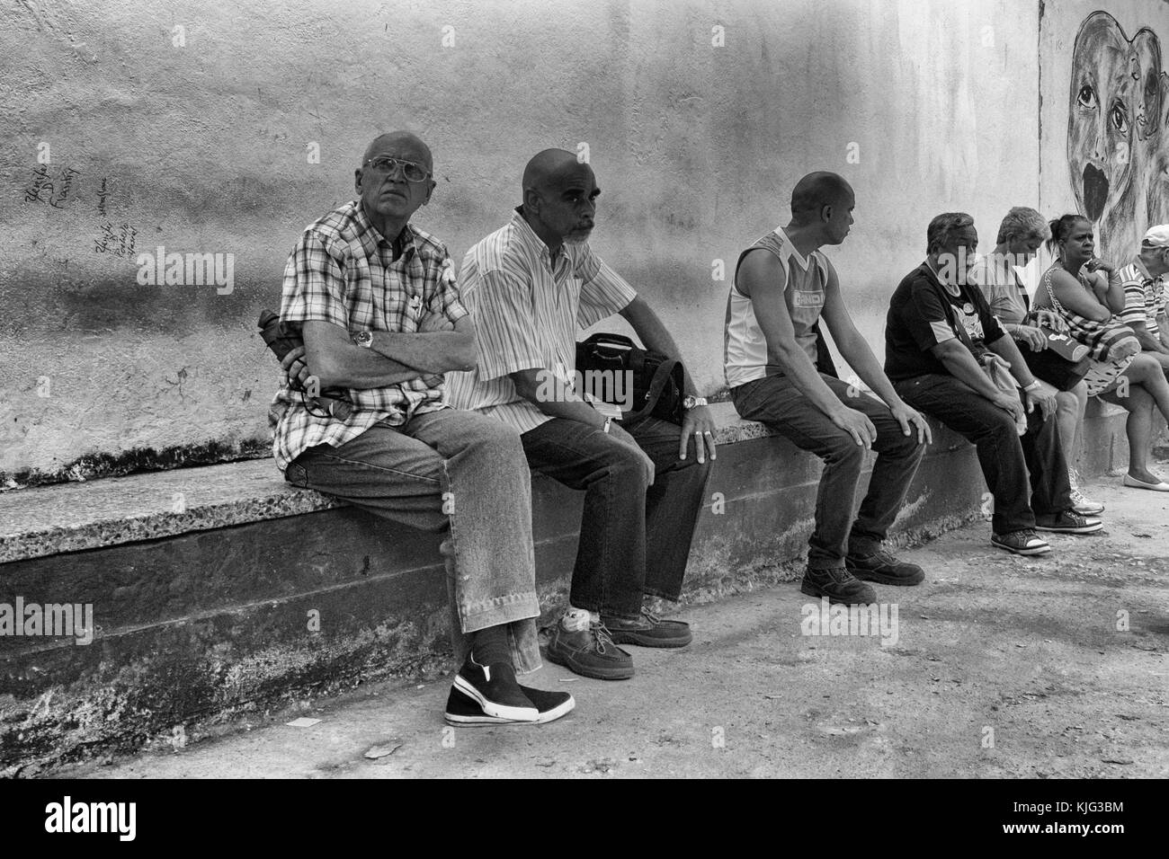 Cuban adults sat waiting for a bus to arrive. Havana Cuba - Stock Image