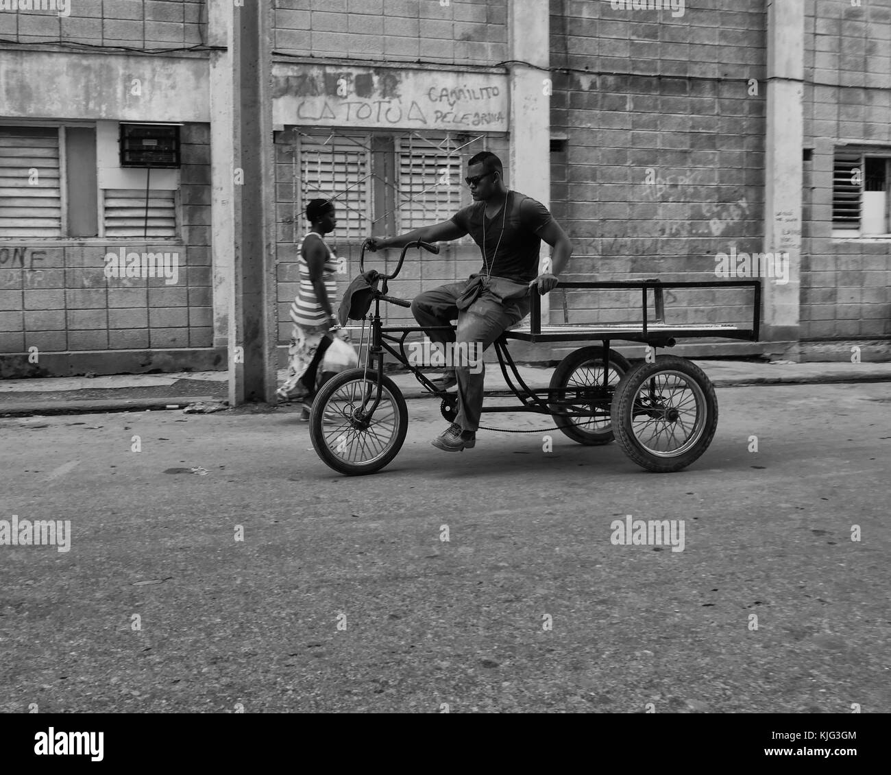 Afro Caribbean Cuban male rides a tricycle past an adult female. Havana, Cuba - Stock Image