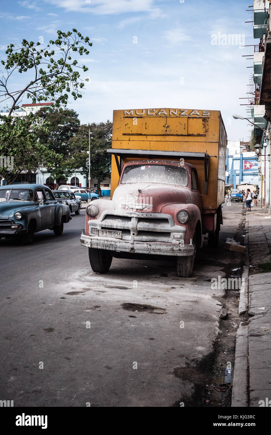 dirty red and yellow painted vintage Cuban truck parked in downtown Havana, Cuba a blue American styled car passes Stock Photo