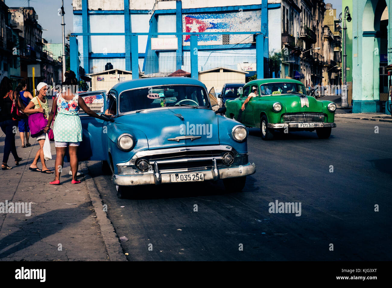 Two Cuban classic taxi cars ply their trade on a central, Havana ...