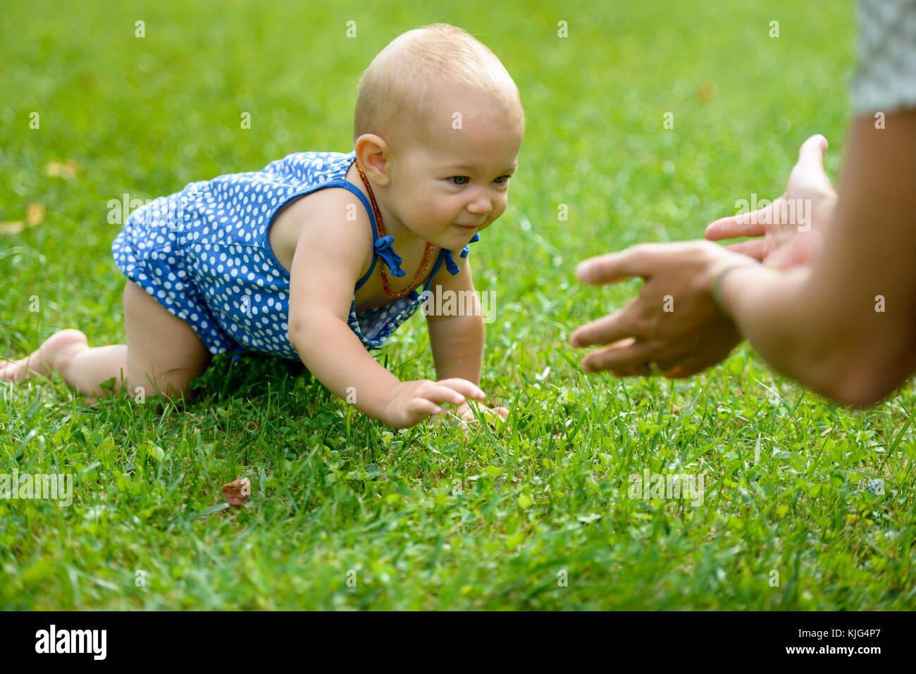 kleines Mädchen krabbelt durch eine Wiese im Grünen, Bayern, Deutschland - Stock Image