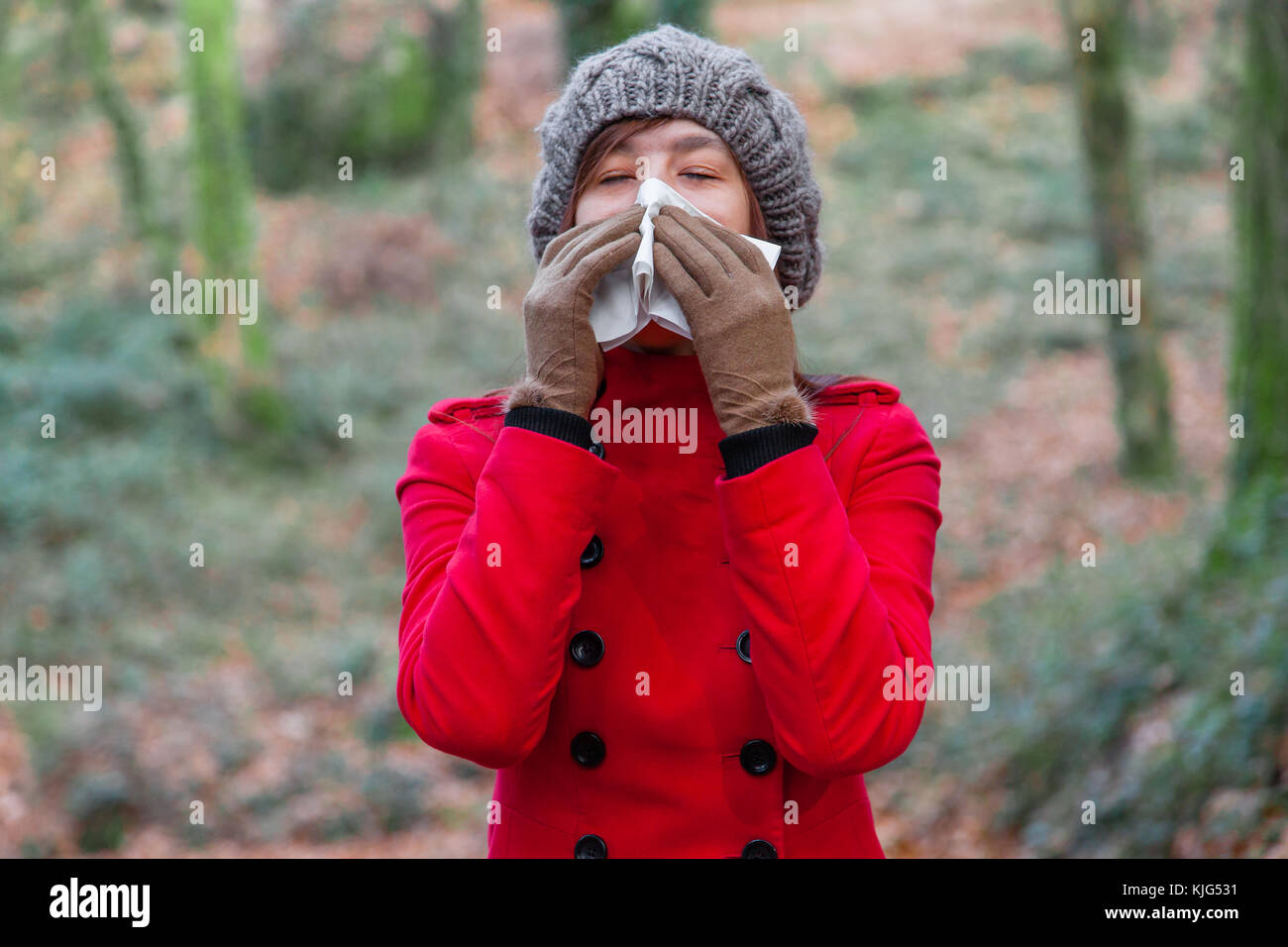 Young woman suffering from cold or flu blowing nose or sneezing on white paper handkerchief in forest wearing a - Stock Image