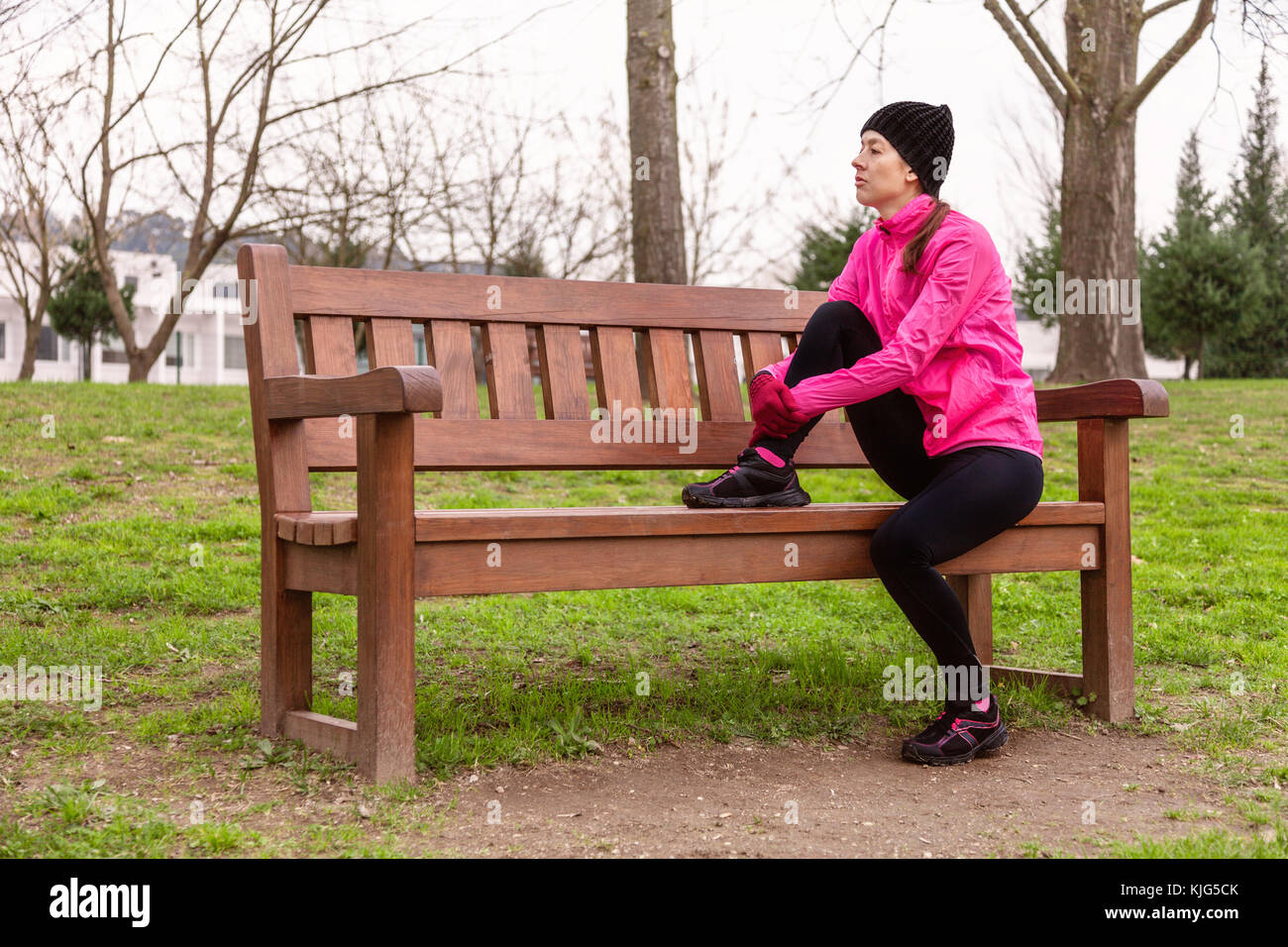 Female athlete tired or depressed resting on a bench on a cold winter day on the training track of an urban park. - Stock Image