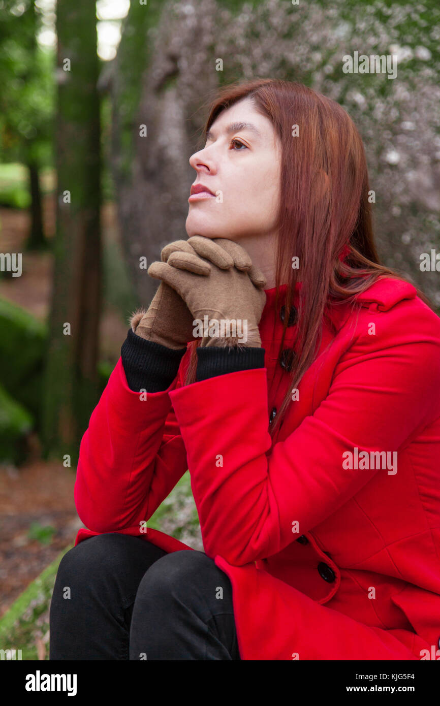 Depressed and sad young woman feeling depression sitting on forest, looking up with melancholic thinking, wearing - Stock Image